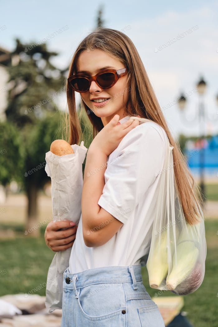 Young pretty smiling girl with baguette bread and vegetables in eco bag happily looking in camera