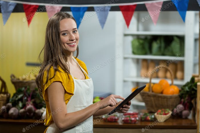 Woman vendor using digital tablet at the counter at grocery store