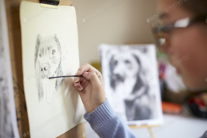Close Up Of Female Teenage Artist Sitting At Easel Drawing Picture Of Dog