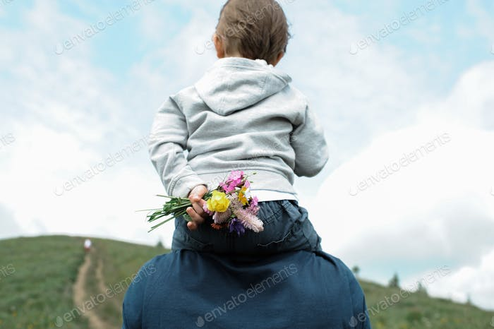 Little boy carried on his father's shoulders hiding wildflowers behind his back.