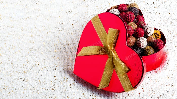 Heart-shaped box with chocolates. Handmade candies. Copy space