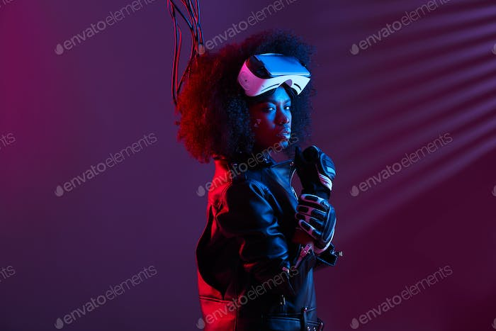 Stylish curly dark haired girl dressed in black leather jacket and gloves is wearing the virtual