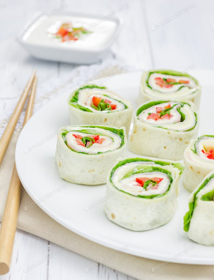 Tortilla roll with soft cheese, chicken ham, and vegetable