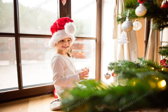 Little girl wearing red hat decorating Christmas tree.