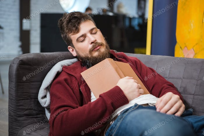 Bearded man sleeping on sofa holding book