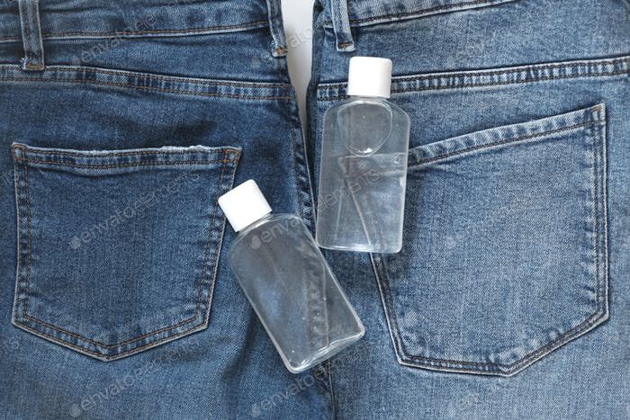 Small portable antibacterial hand sanitizer in pocket jeans.