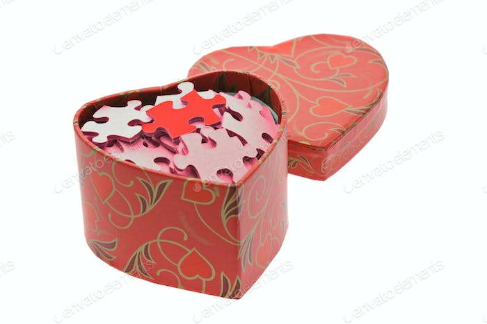 Red and pink jigsaw puzzles in heart shape gift box