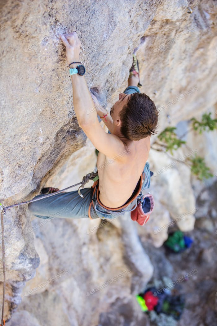 Male rock climber on a face of a cliff, view from above