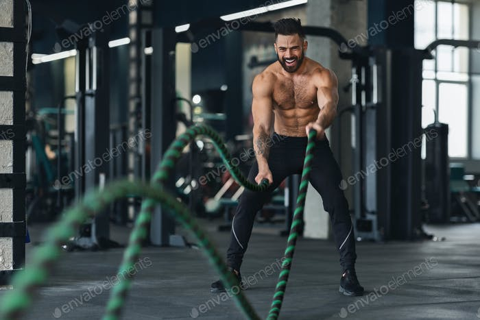 Naked muscular man exercising with battle ropes at gym