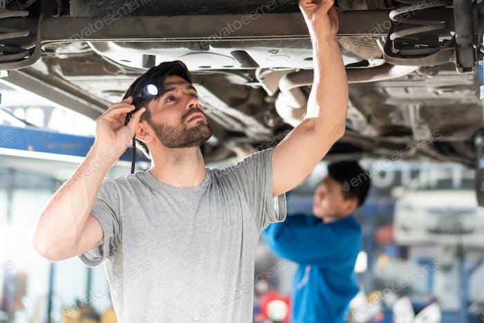 mechanic man using flash light checking under car damage