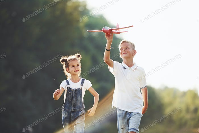 Girl and boy having fun outdoors with red toy airplane in hands