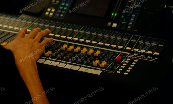 Hand of sound engineer on the control panel
