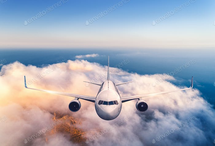 Airplane is flying over the clouds at sunset in summer. Aircraft
