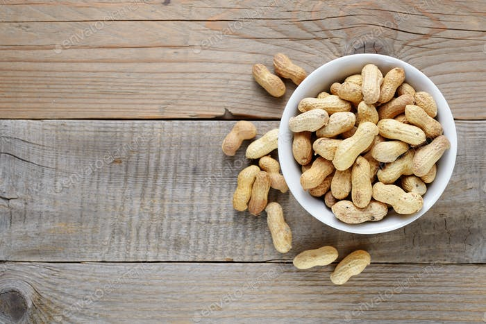 Peanuts in bowl on wooden table top view
