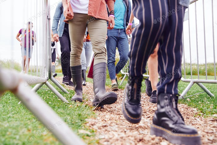 Close Up Of Friends At Entrance To Music Festival Walking Through Security Barriers