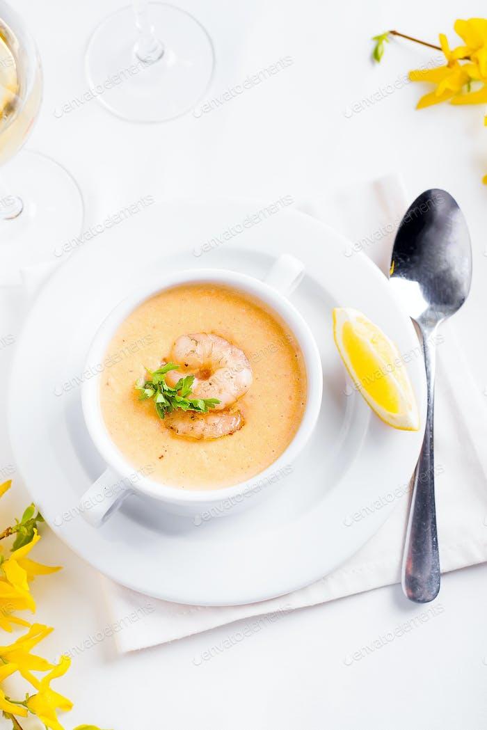 Cremige Kürbissuppe mit Meeresfrüchten und Zitrone auf weißem Hintergrund.