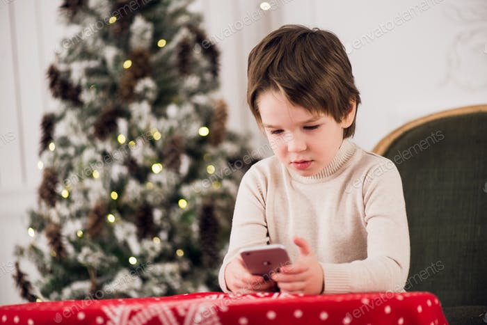 Little happy boy at home using smart phone