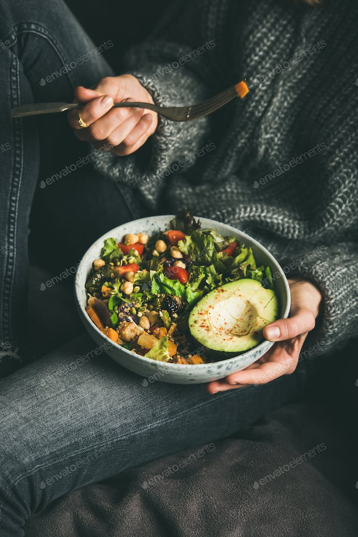 Woman holding bowl with salad, avocado, beans and vegetables