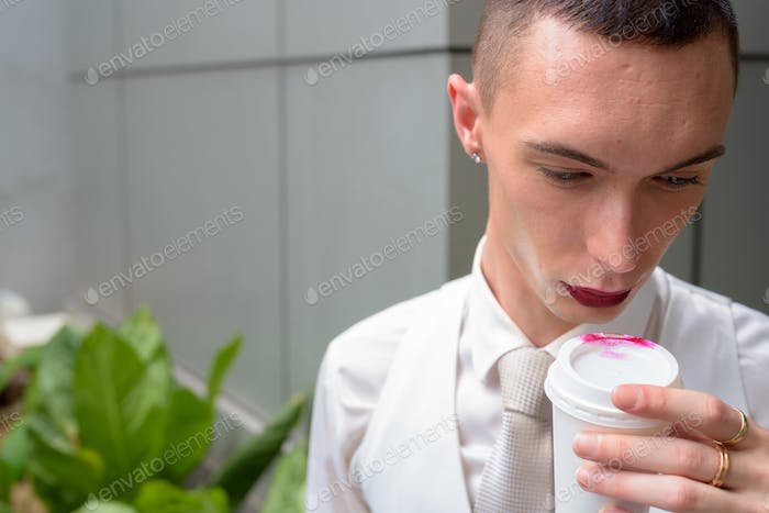 Young androgynous homosexual LGTB businessman drinking coffee