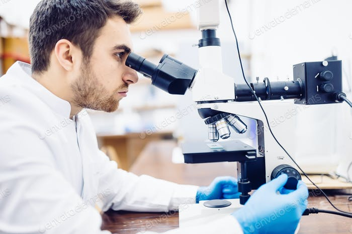 Male scientist, chemist working with microscope in pharmaceutical laboratory, examinating samples