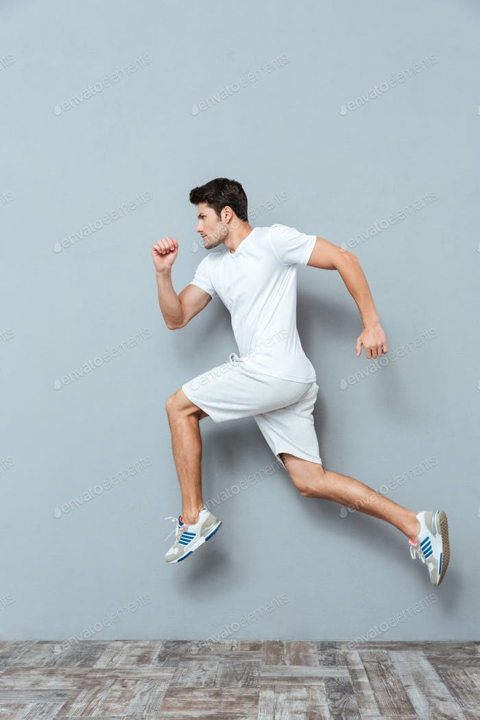 Young serious athletic man jumping isolated