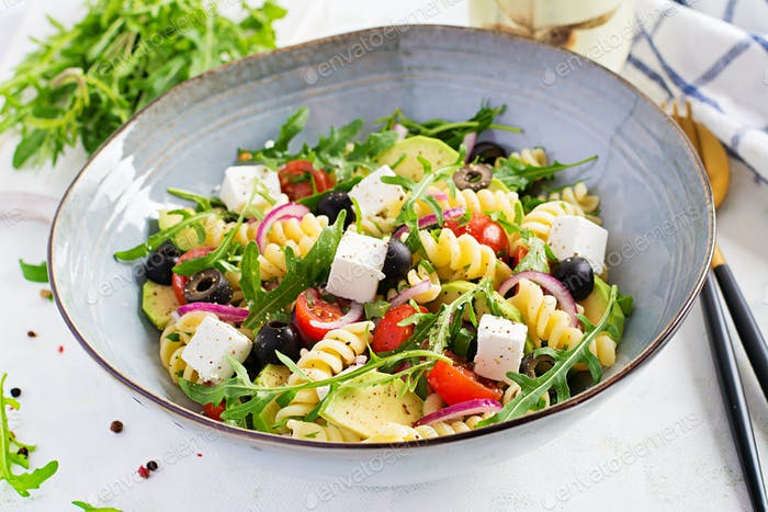 Pasta salad with tomato, avocado, black olives, red onions and cheese feta. Mediterranean cuisine.