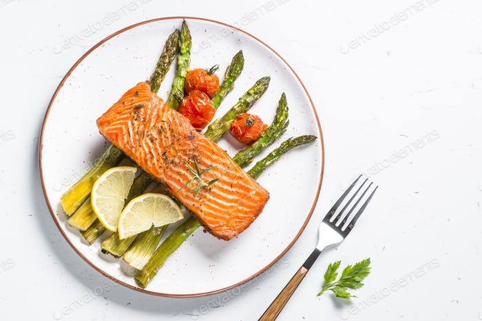 Grilled salmon fish fillet with asparagus on white.