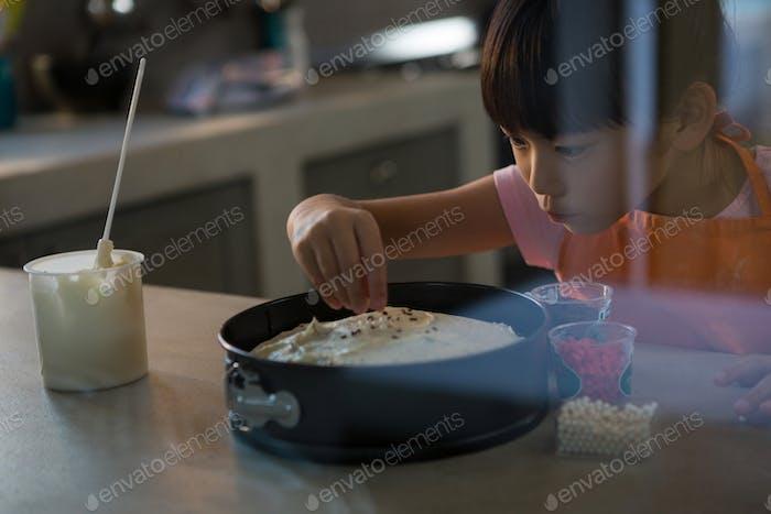 Mädchen dekorieren Kuchen