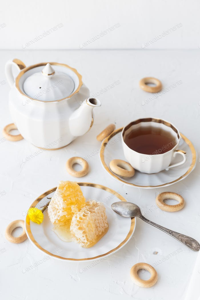 Tea with honey on white background