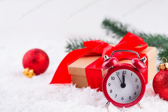 Red old clock with red balls, brown gift box with a large red bow standing in fresh snow against a