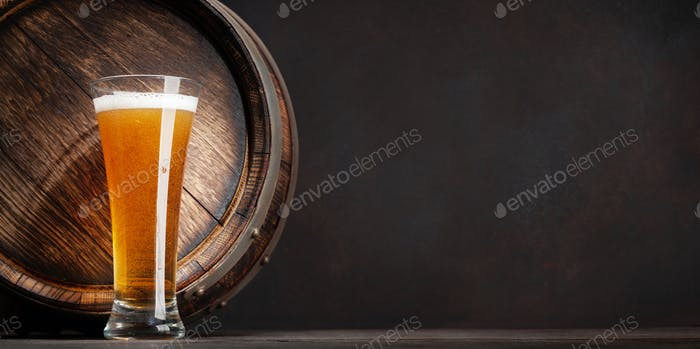 Glass of light lager beer and old wooden barrel