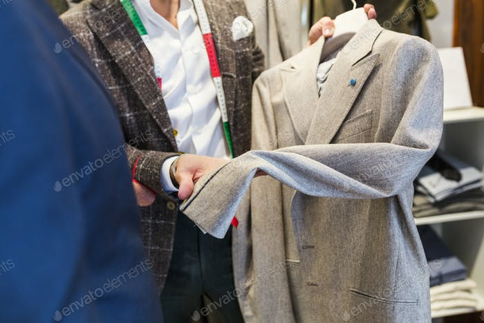 Tailor holding jacket