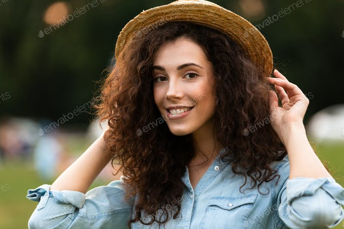 Image of european woman 20s wearing straw hat smiling, while wal