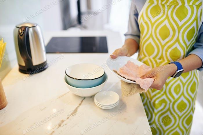 Woman wiping dishware