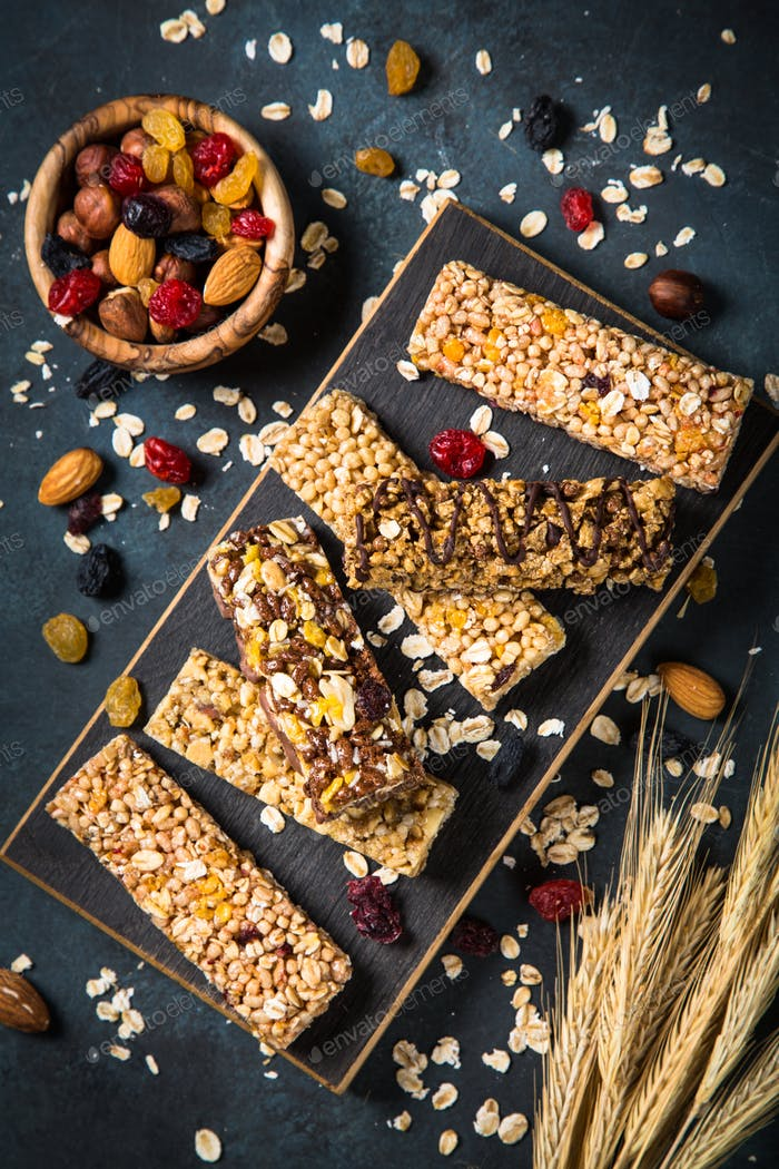 Granola bar with nuts, fruit and berries on black.