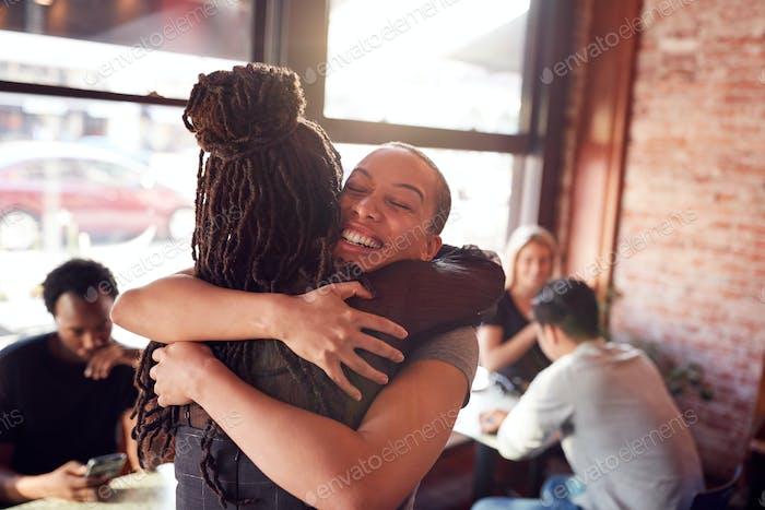 weiblich Freunde Begrüßung jeder andere mit Umarmung als Sie treffen in Coffee Shop