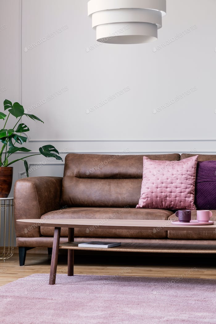Lamp above wooden table in front of leather sofa in bright apart