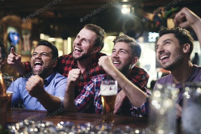 Excited football fans watching soccer in the pub