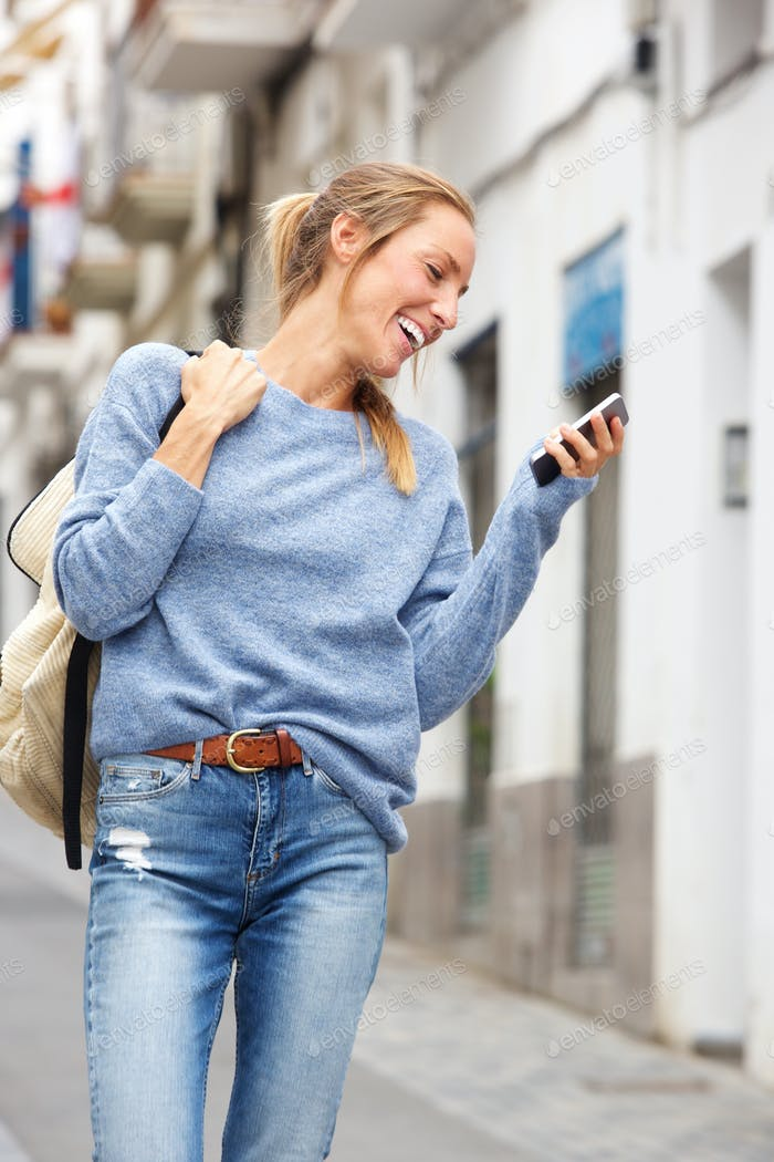 happy young woman walking in city with cell phone