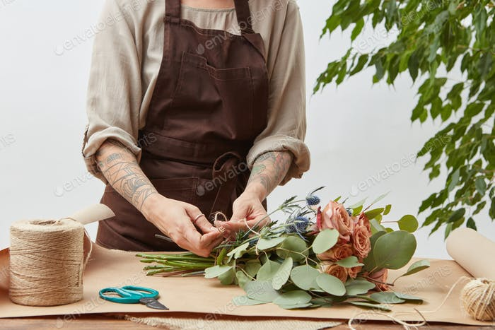 Florist woman is creating fresh rose bouquet on a gray background. Process step by step. Small