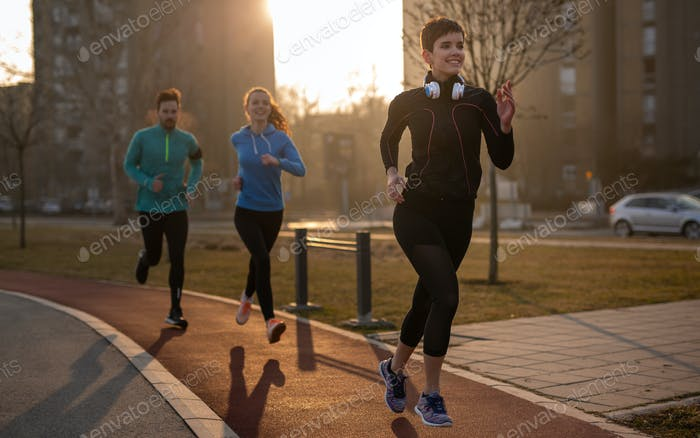 Jogging and running are fitness recreations. Happy group of friends exercising together