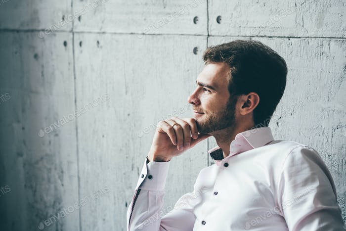 Business man sitting and looking at the window and thinking at modern office.