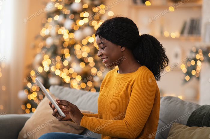 Smiling millennial african american woman with tablet surfing in internet in cozy interior