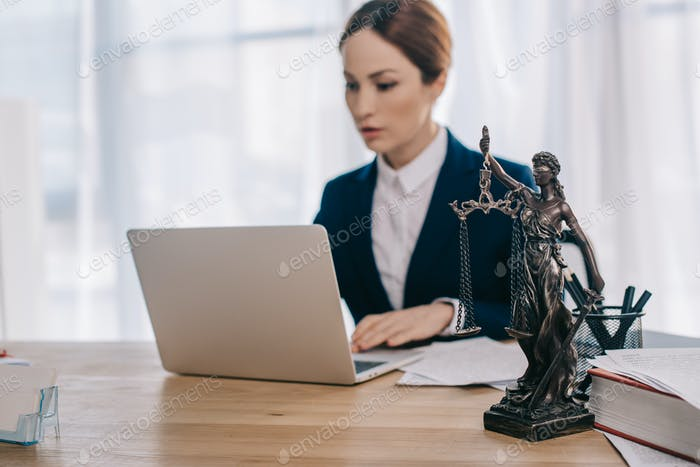 selective focus of female lawyer in suit working on laptop at workplace with femida in office
