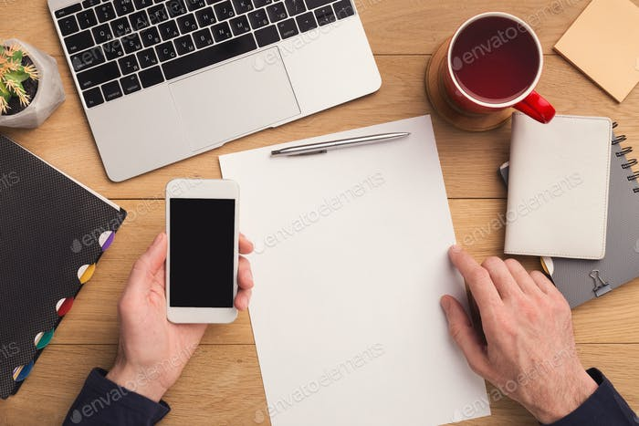 Man writing letter and holding smartphone