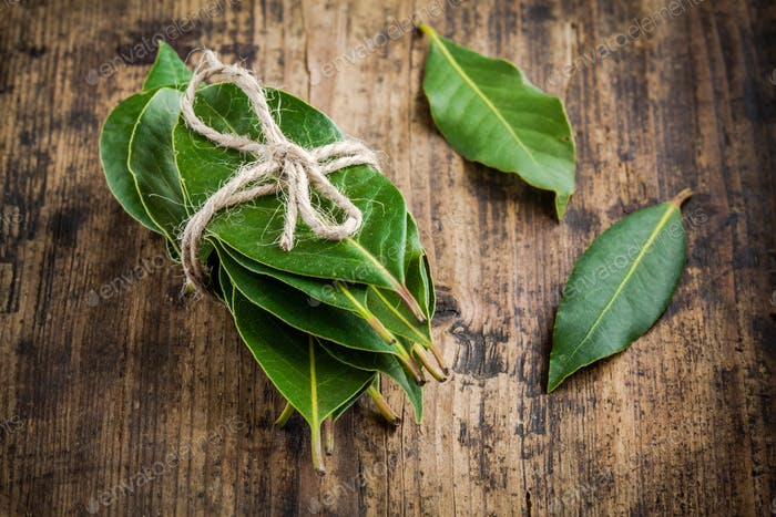 bundle of fresh bay leaves on a wooden background