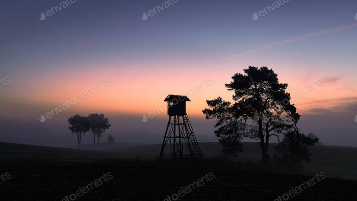 Silhouette of a hunting tower on a field in at dawn.