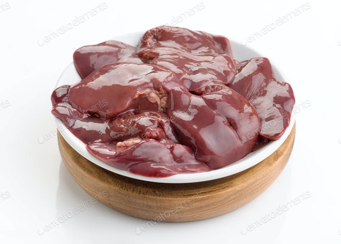 raw chicken liver in white plate on wooden board