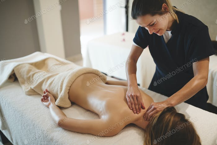 Masseur massaging back of female