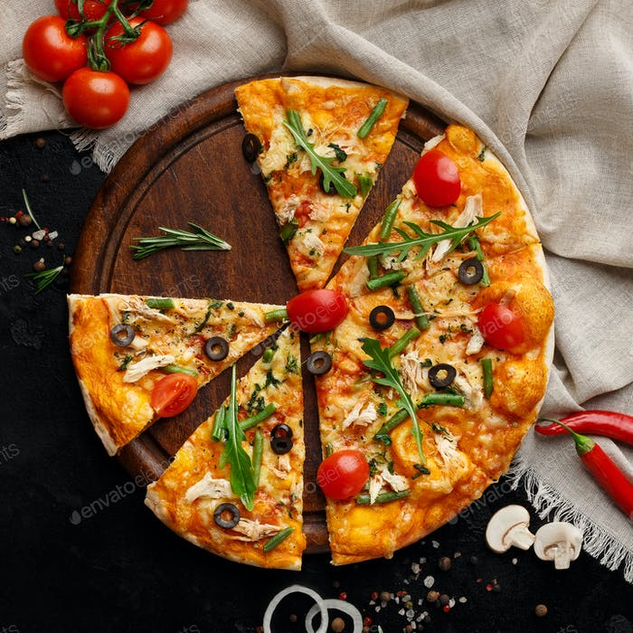 Sliced pizza with vegetables and herbs on cutting board